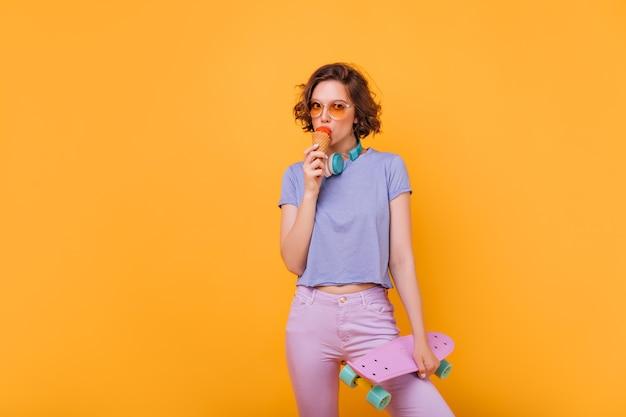 아이스크림을 먹는 짧은 검은 머리와 예쁜 여자. 스케이트 보드와 함께 기쁘게 생각하는 멋진 여자의 실내 사진.