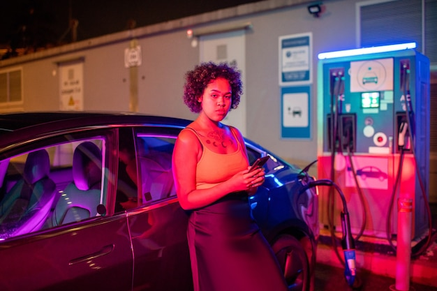 Красивая девушка со смартфоном, стоя у электромобиля