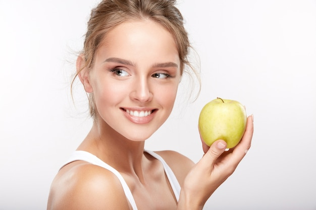 흰색 스튜디오 배경, 치과 개념, 완벽 한 미소, 사과 들고 왼쪽 찾고 눈 하얀 이빨을 가진 예쁜 소녀.