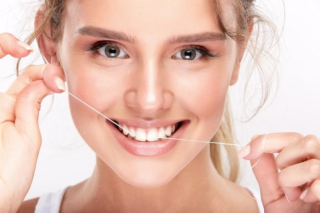 白いスタジオの背景に真っ白な歯、歯科のコンセプト、完璧な笑顔、カメラを見て、クローズアップ、デンタルフロスを使用してかわいい女の子。