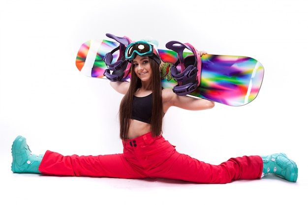 Pretty girl with snowboard on sholders do the splits