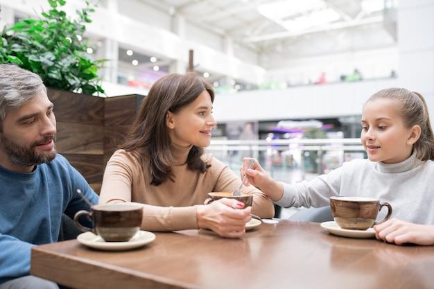 カフェで家族で休憩中に彼女の母親のカップからカプチーノの泡を取ってスプーンでかわいい女の子