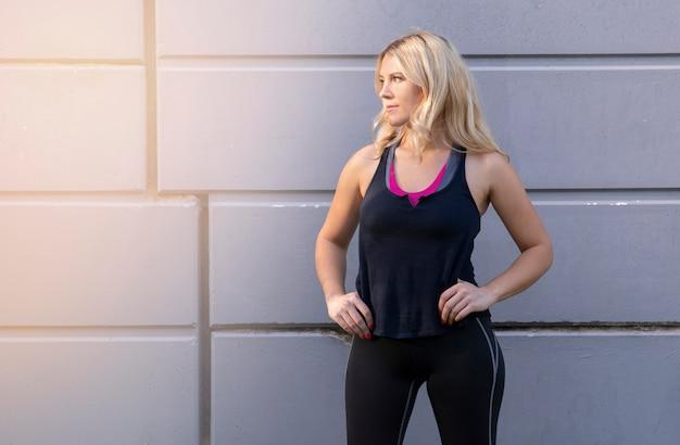 회색 벽 앞에서 운동복과 예쁜 여자