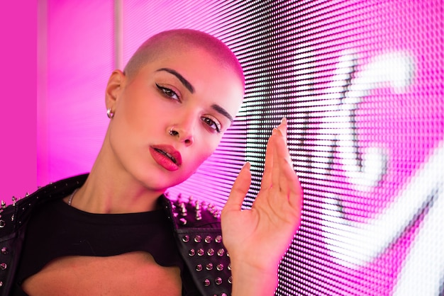 Красивая девушка в стильной одежде позирует возле светодиодных фонарей - портрет красивой женщины