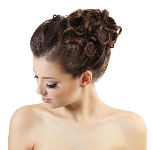 スタイリッシュな巻き毛のかわいい女の子。白で隔離の高角度の肖像画