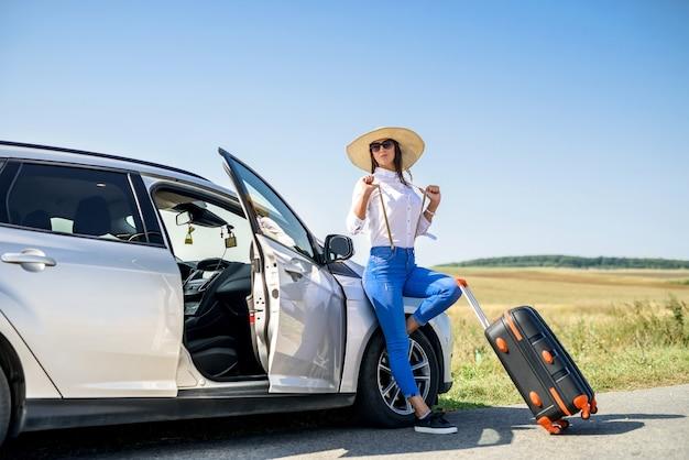 車の近くに立っているスーツケースと彼女の夢の旅のためのwiatを持つかわいい女の子
