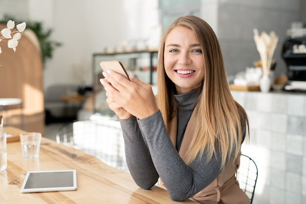 Pretty girl with toothy smile looking at you while sitting by table in cafe and scrolling or texting in smartphone