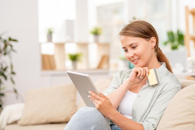 タッチパッドとプラスチックカードを使って、購入する商品を選択しながらオンラインショップで商品を探しているかわいい女の子