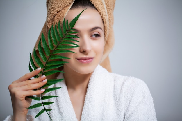 Pretty girl with a towel on his head and a green leaf after taking a shower