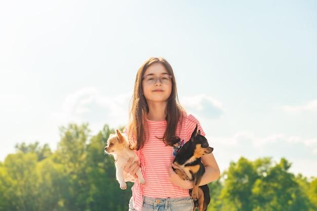 自然に 2 匹のチワワ犬を持つかわいい女の子。ペットの犬を腕に抱えた 10 代の少女。