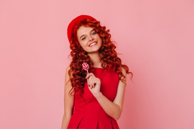 Bella ragazza con capelli ondulati esamina la macchina fotografica sullo spazio rosa. donna con gli occhi azzurri vestita in abito rosso in posa con lecca-lecca.