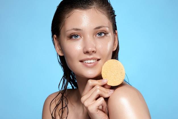 Pretty girl with wet face keeps beige sponge near her shoulder and smiling to the camera