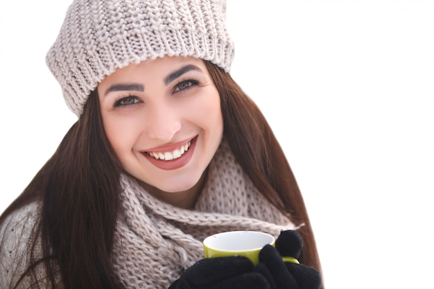 Pretty girl in the woods in winter background with tea cup.