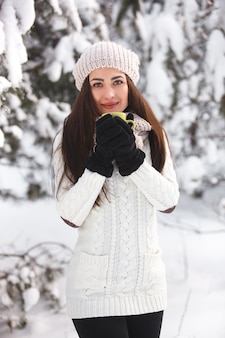 Pretty girl in the woods in winter with tea cup.