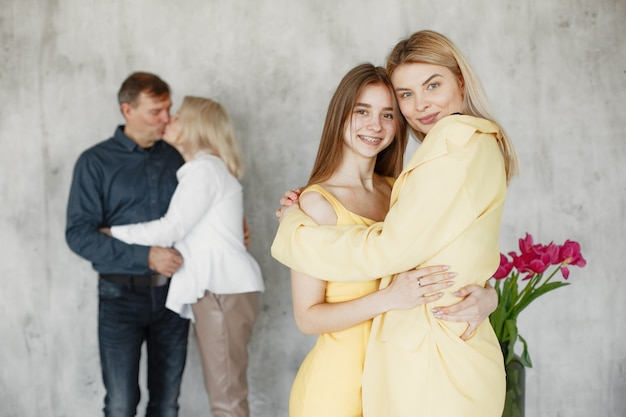 Pretty girls embracing and parents hugging blurred behind.