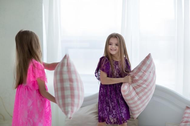 ピンクと紫のドレスを着たかわいい女の子はクッションの戦いを持っています