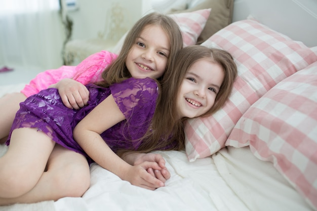 Pretty girls in pink and purple dresses lay in bed