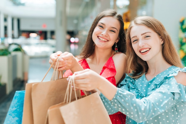 Pretty girls posing with shopping bags