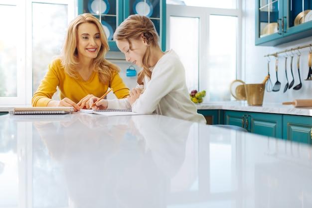 Довольно рада белокурая стройная мать улыбается и смотрит на свою дочь, пишущую в ее блокноте