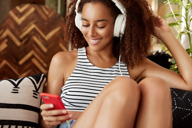 Pretty glad dark skinned woman shares media in social networks, feels comfortable on sofa, chats online on mobile phone, connected to internet. relaxed african american woman enjoys recreation