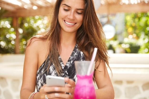 魅力的な外観のかなり嬉しい女性モデルは、昼休みの間に歩道のカフェに座って、スマートフォン経由でソーシャルネットワークで写真を表示し、果物のスムージーを飲み、幸せそうな顔をしています。人とテクノロジー