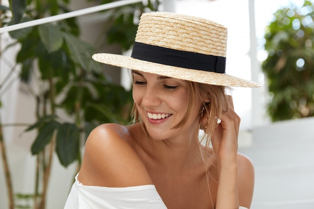 Pretty glad female wears straw hat, shows her tanned bare shoulder, smiles with happy expression as looks joyfully aside, spends summer vacations abroad. lovely young woman enjoys good resort alone