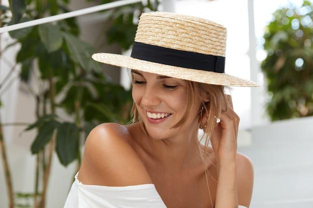 かなり嬉しい女性は麦わら帽子をかぶって、日焼けした裸の肩を見せて、嬉しそうに笑って幸せそうな表情で笑って、外で夏休みを過ごします。素敵な若い女性は一人で良いリゾートを楽しんでいます