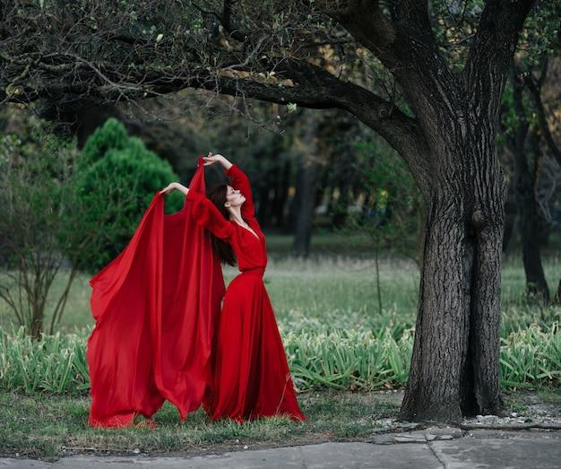 自然の新鮮な空気の木の近くでポーズをとるかなり魅力的な女性
