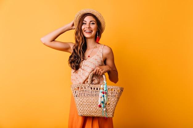 麦わら帽子に触れる可愛らしいグラマラスな女の子。夏のバッグと楽しい若い女性のスタジオポートレート。