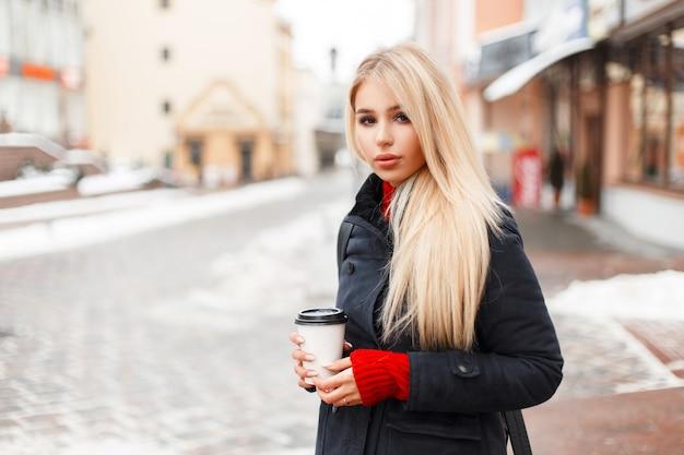 Довольно гламурная модель девушка с кофе в модном зимнем винтажном пальто с сумкой гуляет по городу