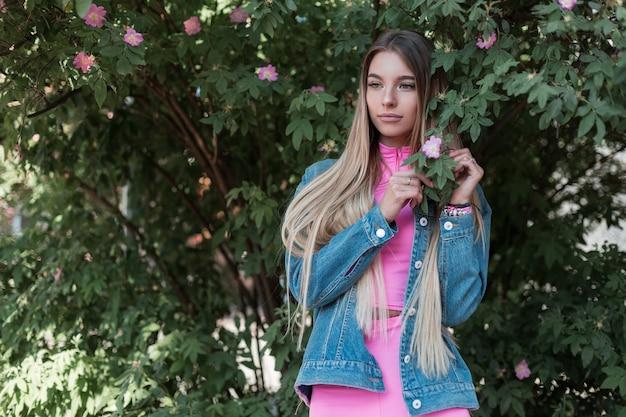 흰색 스 니 커 즈에 핑크 탑에 세련 된 핑크 반바지에 빈티지 데님 재킷에 꽤 매력적인 젊은 금발 여자 야외 금속 벽 근처에 앉아있다. 주말을 즐기는 도시 소녀 모델. 여름 스타일.