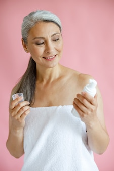 Pretty grey haired asian woman looks at body care product on pink background
