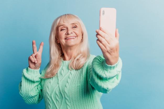 自撮りスマートフォンを取っているかなり白髪の老婆は、青い背景の上に分離されたvサインを作成します
