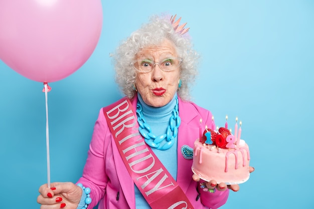 Pretty grey haired wrinkled woman keeps lips folded wears bright makeup holds delicious cake celebrates 102nd birthday going to blow candles and make wish holds inflated balloon. party time concept