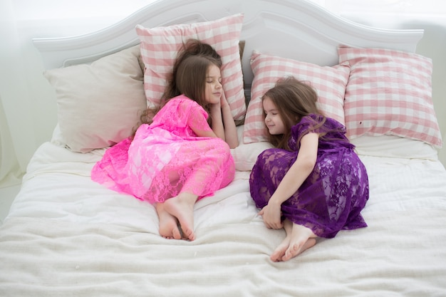 Pretty grils in pink and purple dresses sleep in bed