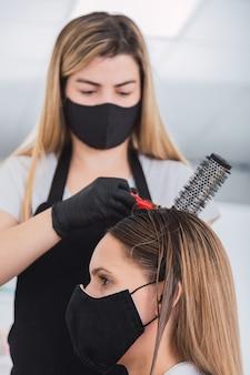 Довольно парикмахер с черной защитной маской и латексными перчатками - парикмахер укладывает молодую женщину в защитной маске.