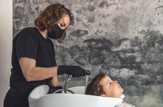 검은 색 보호 마스크와 라텍스 장갑이 달린 예쁜 미용사가 샤워를 준비하여 아이의 머리카락을 씻습니다. 프리미엄 사진