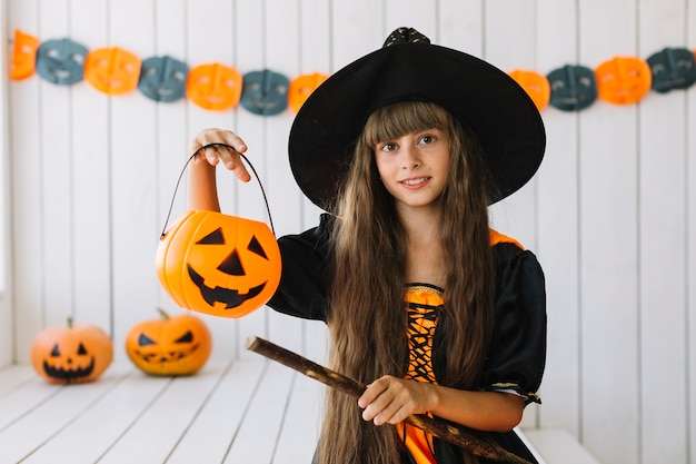 Pretty halloween witch with spooky lantern and broom