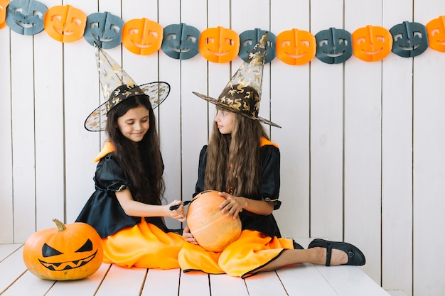 Pretty halloween witches decorating pumpkin