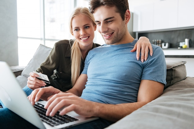 Pretty handsome man and woman using laptop computer