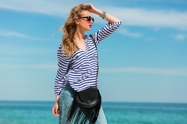 かなり幸せな若い女性笑って、太陽が降り注ぐビーチで楽しんで