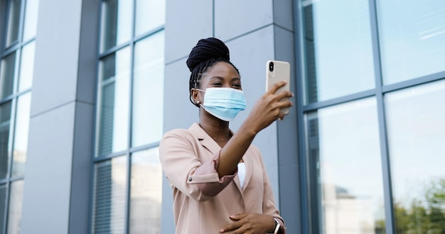 Pretty happy african american young woman in medical mask having videochat on smartphone outdoor at business building. cheerful beautiful female talking and videochatting via webcam on mobile phone.