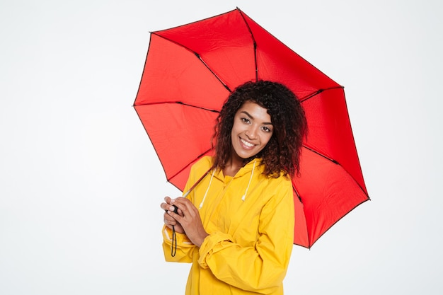 Pretty happy african woman in raincoat posing with umbrella