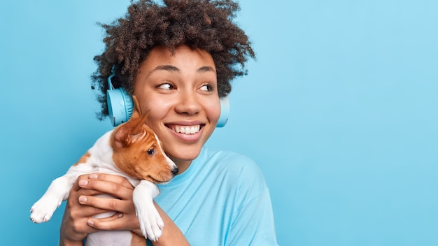 Pretty happy afro american woman holds small puppy in hands enjoys spending free time with favorite pet looks gladfully aside listens music via wireless headphones isolated over blue wall