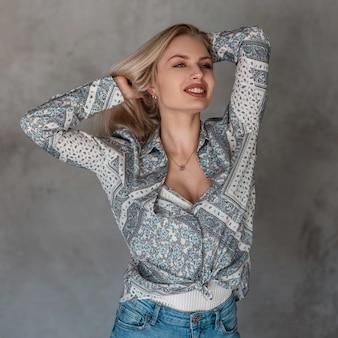 灰色の壁の近くの部屋でポーズをとってスタイリッシュなジーンズの白いtシャツのパターンとヴィンテージの灰色のシャツのかわいい笑顔でかなり幸せな美しい若いブロンドの女性