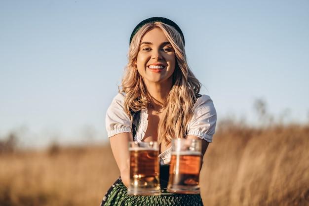 Довольно счастливая блондинка в дирндль, традиционное фестивальное платье, держит две кружки пива на открытом воздухе в поле