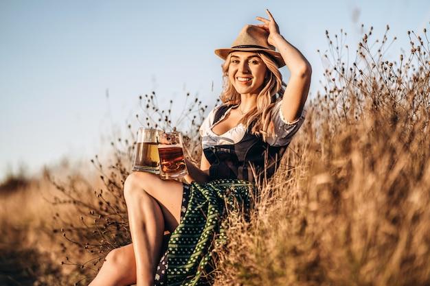 Довольно счастливая блондинка в дирндле, традиционном фестивальном платье, сидит с двумя кружками пива на открытом воздухе в поле