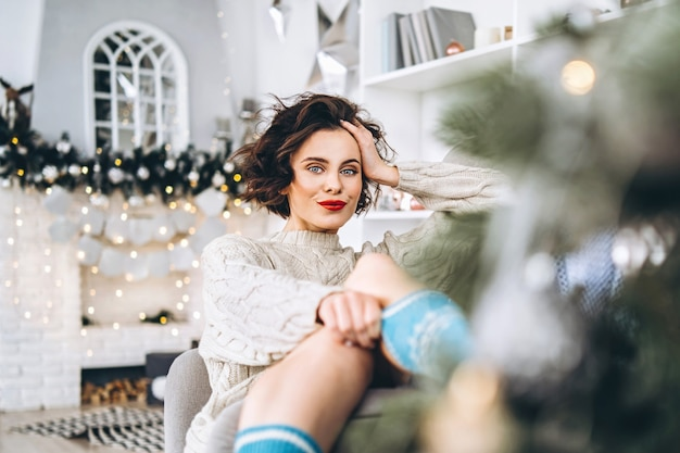 Pretty and happy brunette sitting in warm sweater on the chair with christmas lights behind