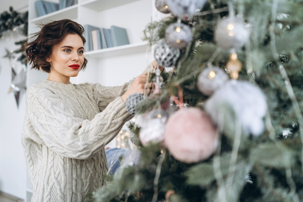 Pretty and happy brunette in warm sweater decorating christmas tree at home