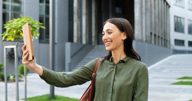 Довольно счастливая кавказская молодая женщина, имеющая видеочат на планшетном устройстве, открытом на улице в городе. радостная красивая женщина разговаривает и видеочат через веб-камеру на гаджет-компьютере. за пределами.
